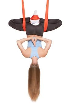 Jonge vrouw die anti-zwaartekracht luchtyoga in hangmat op witte muur doet