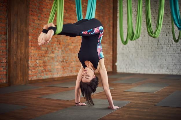 Jonge vrouw die antigravity yogaoefeningen in een zolderbinnenland maken
