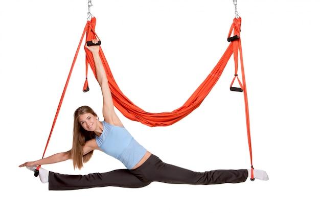 Jonge vrouw die antigravity yogaoefeningen in het uitrekken van streng maken