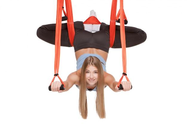 Jonge vrouw die antigravity yogaoefeningen in zich uitrekt streng maakt