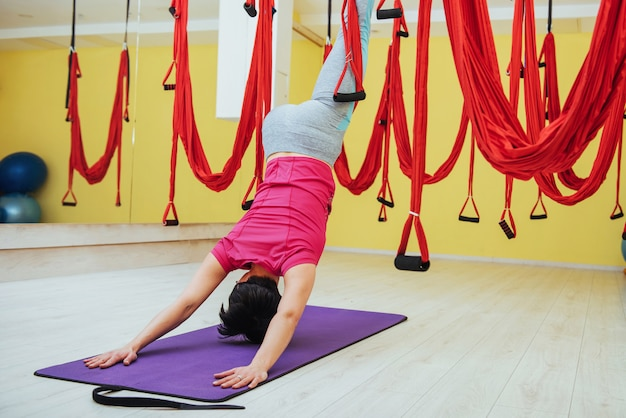 Jonge vrouw die antigravity yogaoefeningen maakt