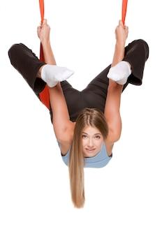 Jonge vrouw die antizwaartekracht luchtyoga doen