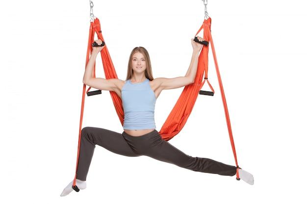 Jonge vrouw die antizwaartekracht luchtyoga in hangmat op een naadloos wit doen