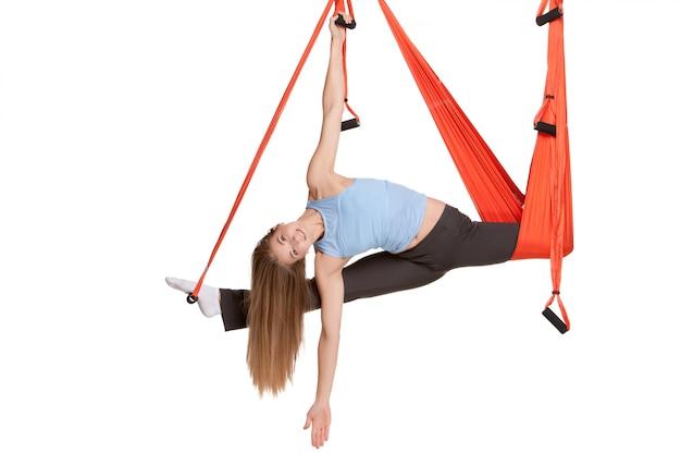 Jonge vrouw die antizwaartekracht luchtyoga in hangmat op een naadloze witte muur doen