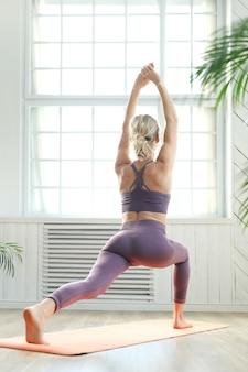 Jonge vrouw die arm en been het uitrekken in het yogacentrum doen zich