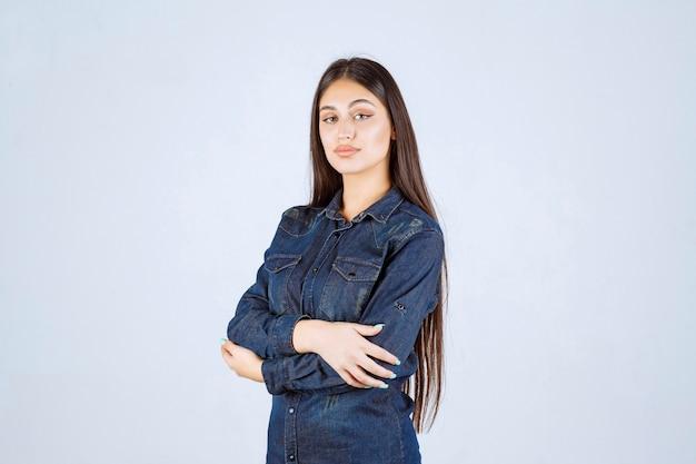 Jonge vrouw die armen kruist en professionele poses geeft