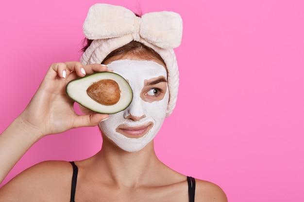 Jonge vrouw die avocado in handen houdt en haar ogen bedekt met fruit, met wit masker op gezicht, opzij kijkt, hoofdband met boog draagt die over roze achtergrond wordt geïsoleerd.