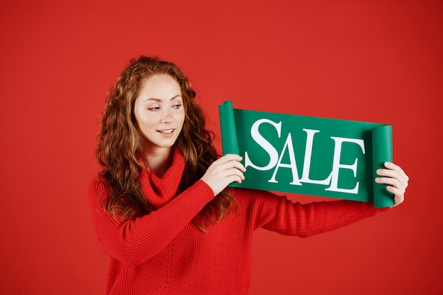 Jonge vrouw die banner van verkoop toont bij studioschot
