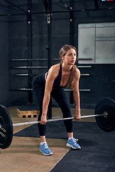 Jonge vrouw die barbell in gymnastiek opheft