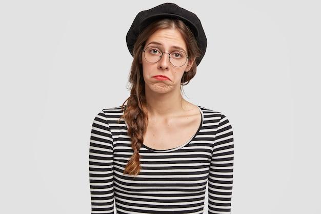 Jonge vrouw die baret en gestreept overhemd draagt