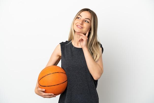 Jonge vrouw die basketbal speelt over een geïsoleerde witte muur die een idee denkt terwijl ze omhoog kijkt