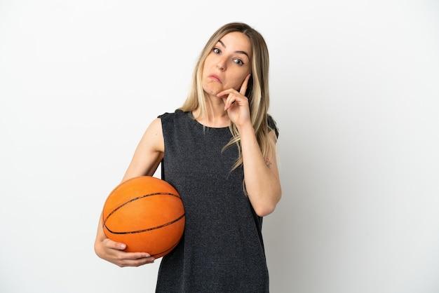 Jonge vrouw die basketbal speelt over een geïsoleerde witte muur die een idee denkt