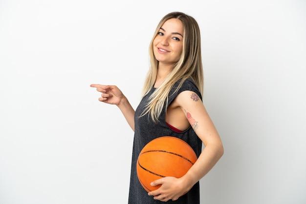 Jonge vrouw die basketbal speelt over een geïsoleerde witte muur die met de vinger naar de zijkant wijst