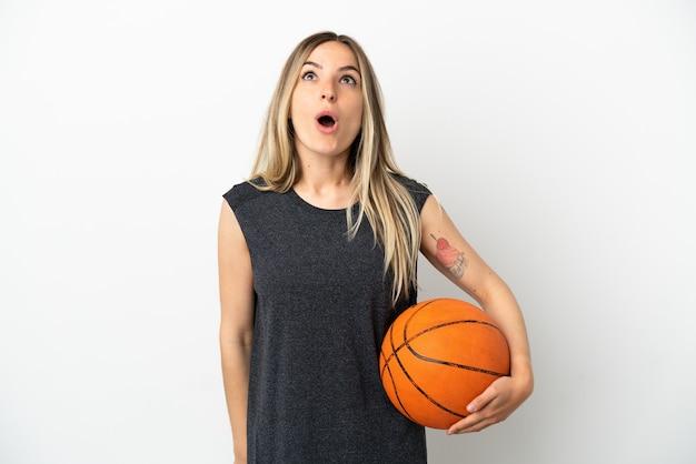 Jonge vrouw die basketbal speelt over een geïsoleerde witte muur die omhoog kijkt en met een verbaasde uitdrukking