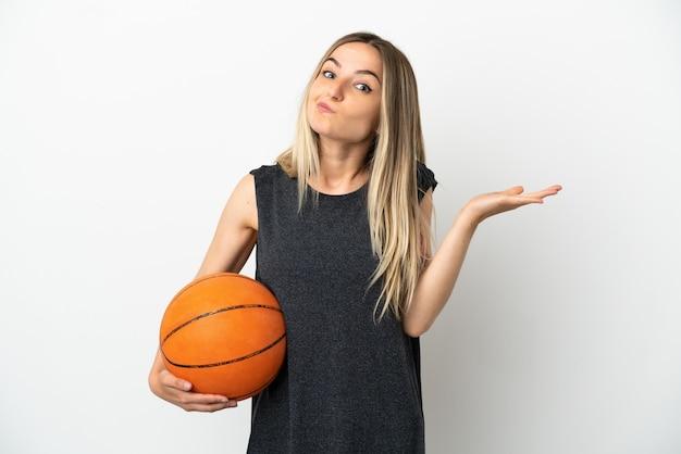 Jonge vrouw die basketbal speelt over een geïsoleerde witte muur die twijfelt terwijl ze haar handen opsteekt