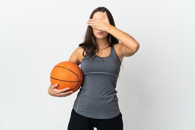 Jonge vrouw die basketbal speelt over geïsoleerde witte achtergrond die ogen bedekt door handen. wil je iets niet zien
