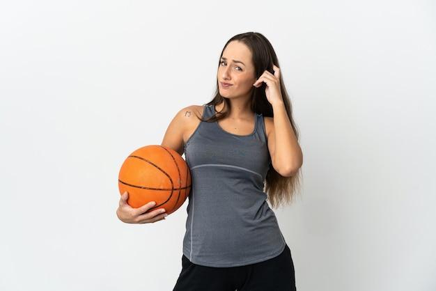 Jonge vrouw die basketbal speelt over geïsoleerde witte achtergrond die twijfels heeft