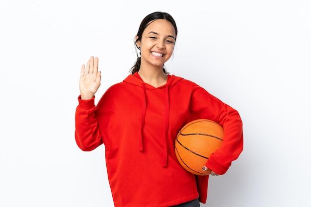 Jonge vrouw die basketbal speelt over geïsoleerde witte muur die met hand met gelukkige uitdrukking groet