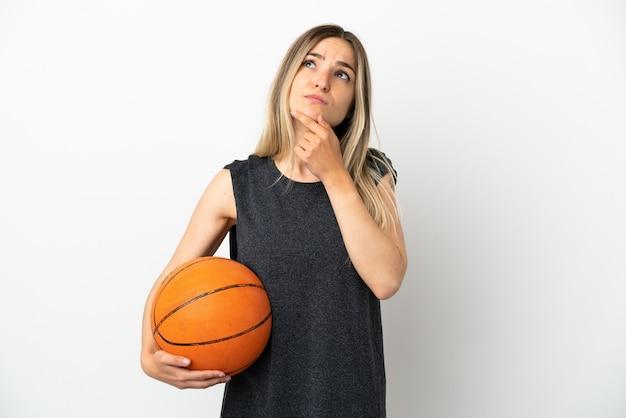 Jonge vrouw die basketbal speelt over geïsoleerde witte muur die twijfels heeft