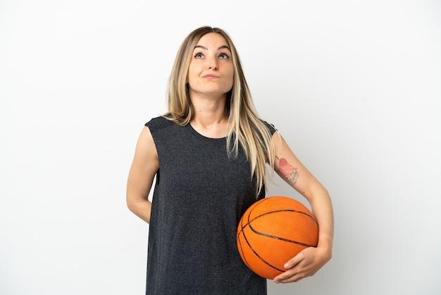 Jonge vrouw die basketbal speelt over geïsoleerde witte muur en omhoog kijkt