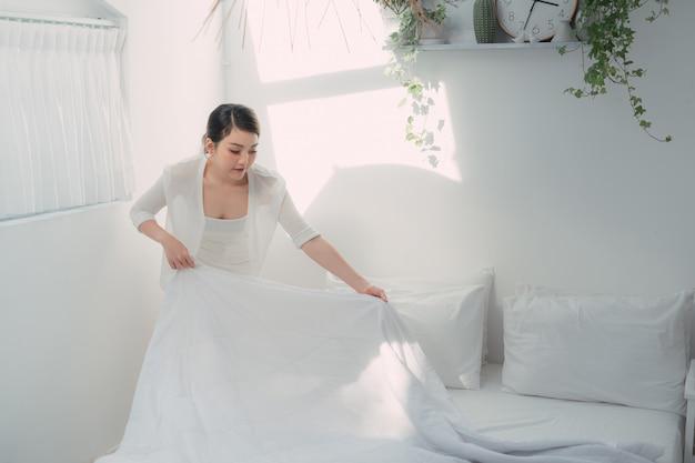 Jonge vrouw die bed opmaakt en kamer in de ochtend organiseert,