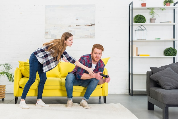 Jonge vrouw die bedieningshendel van zijn vriend neemt die het videospelletje speelt
