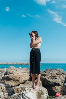 Jonge vrouw die beeld van mooie aard neemt die zich op rots dichtbij overzees bevindt