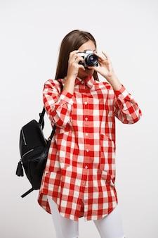 Jonge vrouw die beelden op camera neemt die op witte muur wordt geïsoleerd