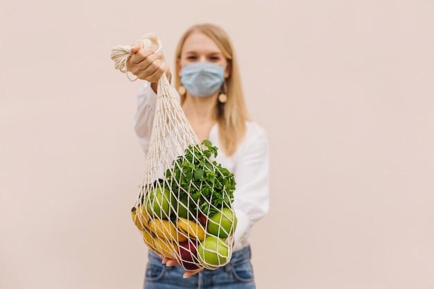 Jonge vrouw die beschermend gezichtsmasker draagt ter preventie van coronavirus