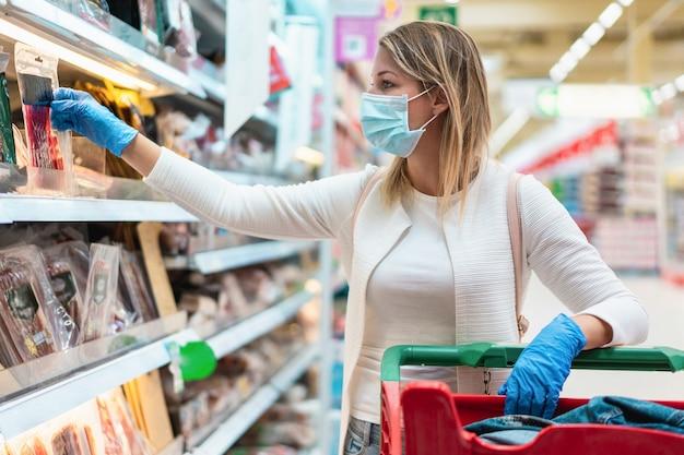 Jonge vrouw die beschermend masker in supermarkt draagt tijdens de uitbraak van het coronavirus