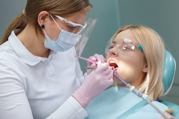 Jonge vrouw die beschermende bril draagt terwijl tandarts haar tanden onderzoekt