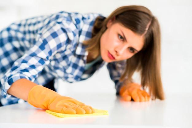 Jonge vrouw die beschermende handschoenen draagt die het witte bureau schoonmaken