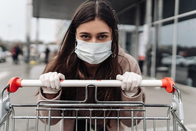 Jonge vrouw die beschermingsgezichtsmasker draagt tegen coronavirus 2019-ncov die een boodschappenwagentje duwt.