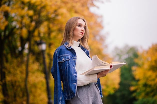 Jonge vrouw die beschermt tegen het coronavirus tijdens het wandelen in het park. herfst achtergrond.