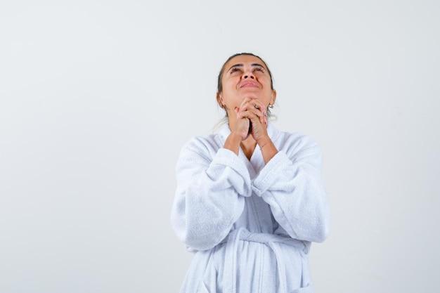 Jonge vrouw die biddend gebaar in badjas toont en hoopvol kijkt
