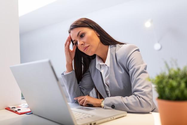 Jonge vrouw die bij bureau voor laptop werkt die aan chronische dagelijkse hoofdpijn lijdt