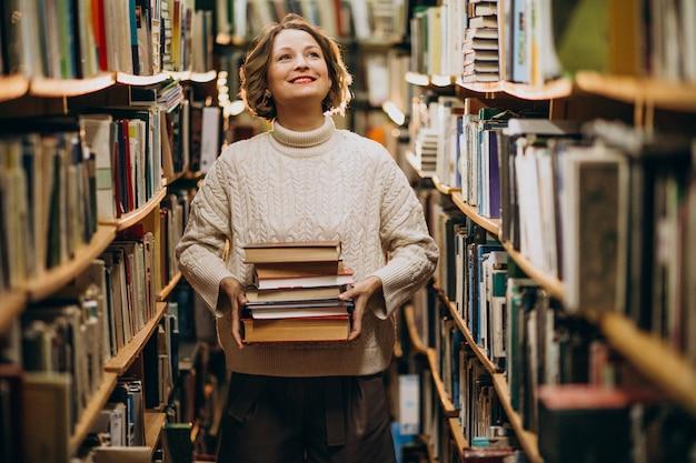 Jonge vrouw die bij de bibliotheek bestudeert