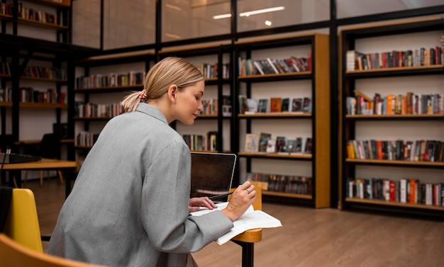 Jonge vrouw die bij de bibliotheek studeert
