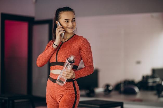 Jonge vrouw die bij de gymnastiek met gewicht uitoefent