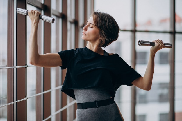 Jonge vrouw die bij de gymnastiek uitoefent
