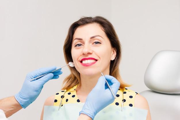Jonge vrouw die bij de tandartsbenoeming glimlacht.