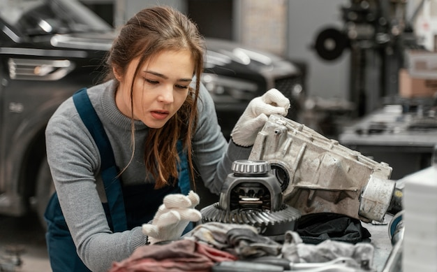 Jonge vrouw die bij een autodienst werkt