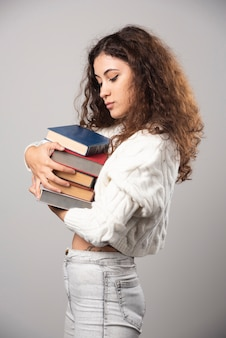 Jonge vrouw die bij een stapel boeken op een grijze muur toont. hoge kwaliteit foto