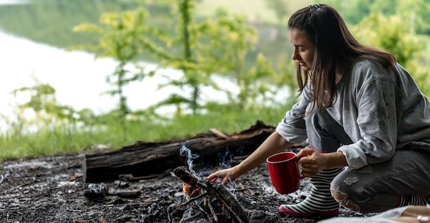 Jonge vrouw die bij het vuur rust met een kopje verwarmende drank in het bos bij de rivier
