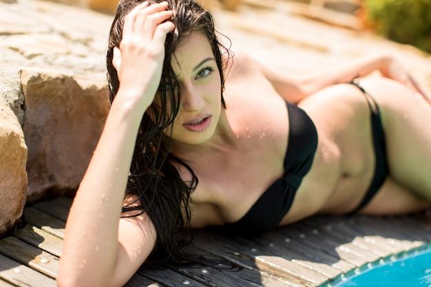 Jonge vrouw die bij het zwembad legt