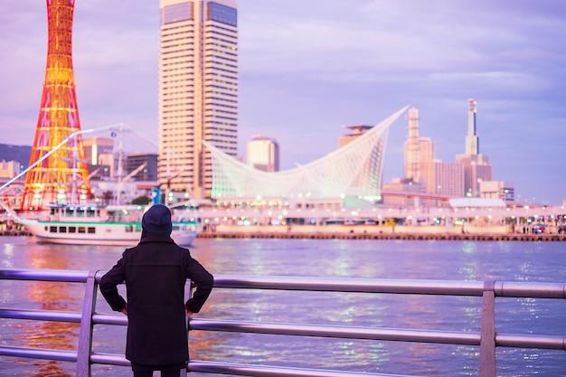 Jonge vrouw die bij kobe-haven dichtbij osaka, gelukkige aziatische reiziger reizen die mooie moderne gebouwen zonsondergang bekijken. landmark en populair voor toeristische attracties in kobe, hyogo, japan. azië travel concept