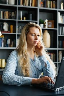 Jonge vrouw die bij laptop aan de lijst werkt. huiswerk. studie en onderwijs. meisje, zakenvrouw