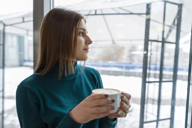 Jonge vrouw die bij onderbreking in koffie met kop van hete drank rust