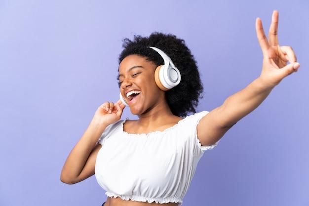 Jonge vrouw die bij purpere het luisteren muziek en het zingen wordt geïsoleerd