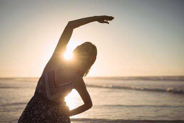 Jonge vrouw die bij strand uitoefent